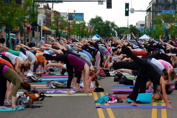 Minneapolis residents practice yoga in a street during the Open Streets festival. Photo credit: bradleypjohnson (flickr). Via Indiana Public Media